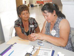 promotora measures blood sugar