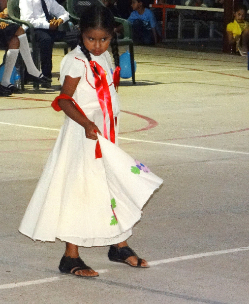 A young solo performer shyly enchants the crowd with her dance..