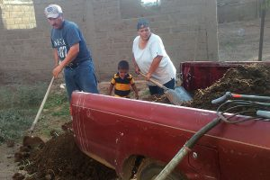 family unloads compost-enriched soil
